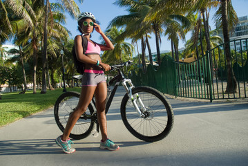 fashionable young woman and her mountain bike in a tropical scene