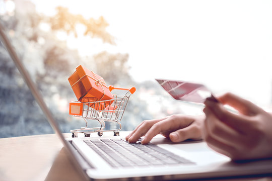 Online shopping concept with woman hand using laptop and looking credit card for purchase order product.