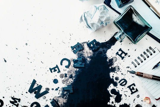 Header with spilled ink, crumpled paper, scattered letters, papers and notepads on a white wooden background. Creative writing concept. Flat lay with copy space.
