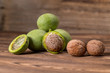 Fresh harvest of walnuts on a wooden background. Green and brown nuts. Shell and peel of walnuts. Walnuts on a wooden surface