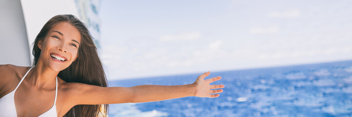 Cruise ship vacation travel fun freedom woman. Asian tourist girl on holidays feeling free with open arms towards ocean water on Caribbean getaway holiday.