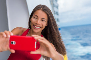 Wall Mural - Selfie photo woman taking cruise travel picture on vacation. Asian girl smiling happy taking a self-portrait on ship balcony deck.