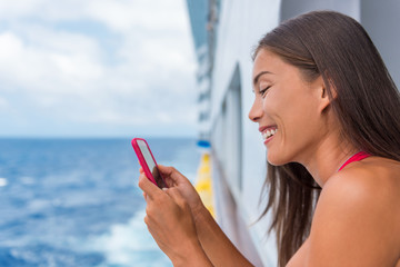 Cruise ship woman using mobile phone on travel vacation at ocean. Asian girl texting sms on wifi on tropical holidays. Internet on international seas concept. Tourist looking at her holiday pictures.