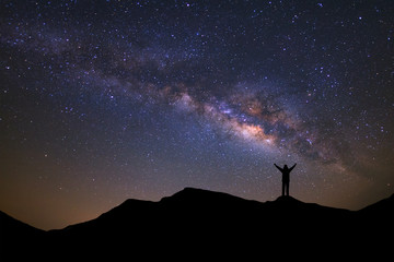 landscape with milky way, Night sky with stars and silhouette of a standing sporty man with raised up arms on high mountain.