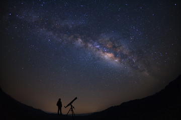 Silhouette of a standing man with telescope watching the wilky way galaxy