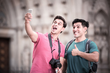 positive men tourists with suitcases are making selfie in unknown city