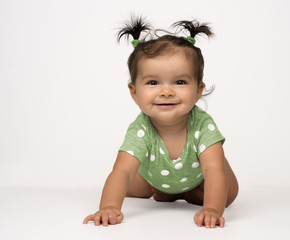 Crawling baby girl in green onesie, on white background