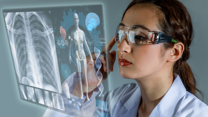 Young female doctor looking at hologram screen. Electronic medical record. Smart glasses. Medical technology concept.