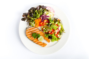 salmon steak grill with fresh salad and lemon onwhite background