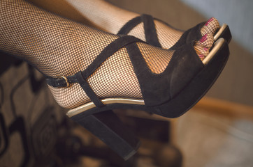 Sexy female legs in fishnet pantyhose stockings in high heels shoes on couch.