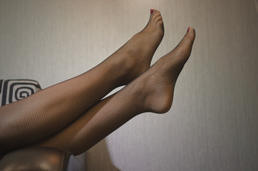 Sexy woman's legs in black pantyhose stockings on the couch.