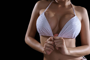 Low key image of upper part of sexy young Asian woman holding white lace bra top isolated on black background