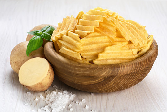 Potato and bowl with potato chips on a wooden background
