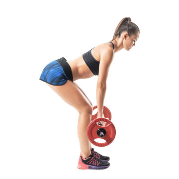 Side view of bend athletic woman doing deadlift exercise in low start position. Full body length portrait isolated on white studio background.