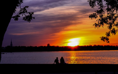 silhouette of two people looking at the sunset