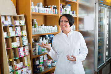 Woman seller in uniform standing with dietary supplements