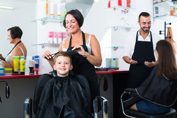 Glad kid sitting in chair and getting hair cut
