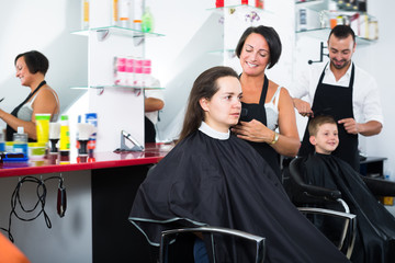 Mature woman hairdresser cutting female client
