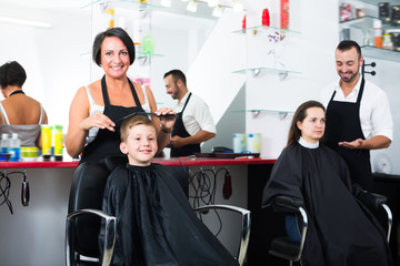 Smiling kid getting hair cut