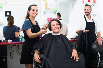 Woman hairdresser cutting female client