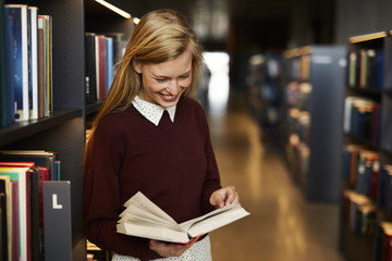 beautiful woman reading book in library, smiling