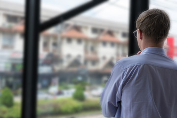 thoughtful businessman look out at the city through window at workplace. back view of young man thinking of new business project at office.