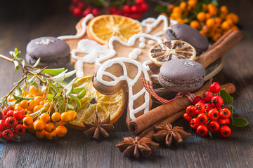 Merry christmas holiday decoration background with ginger man snowflakes snowman and tree cookies. Cinnamon, dry orange, cardamom, star, makarones. Dark wooden table.