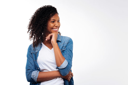 Cheerful woman posing while resting chin on hand