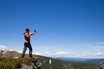 Man on the mountain top taking selfie by cell phone