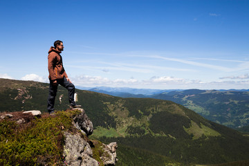 Man standing on the mountain top and looking at horizon