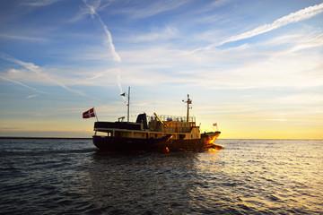 Small sea vessel leaving port of Riga on a beautiful sunset