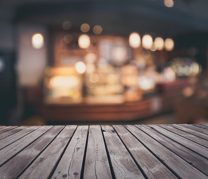 Wooden table top grunge surface over blur cafe interior background