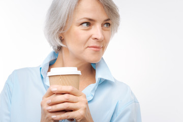 Close up of grey-haired woman holding cup of coffee