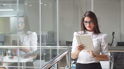 Sexy business lady in glasses uses a tablet in office building.