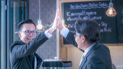 Businessmen giving high five in the concept of success and achievement.