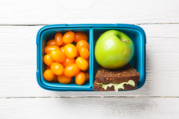 Picture of cherry tomato,apple, sandwich in lunchbox