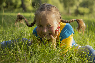 smiling blond girl with funny pigtail sits in grass. She is wearing a yellow T-shirt and a blue sarafan, and she has freckles on her nose.