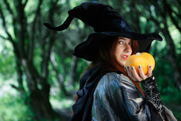 Portrait of witch in black hat with pumpkin
