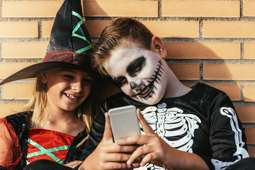 Happy children disguised using the mobile phone in the street.