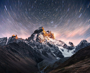 Fantastic starry sky. Snow-capped peaks. Main Caucasian Ridge. Mountain View from Mount Ushba Meyer, Georgia. Europe