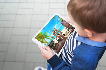 Boy watching video on a tablet. Scene represents the addiction of children playing games and cartoons on the tablet and mobile phones.