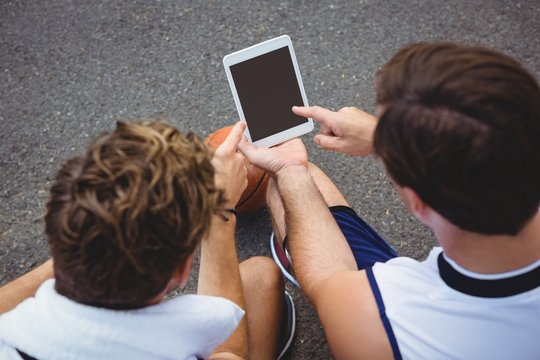 Overhead view of basketball players using digital tablet