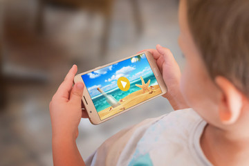 Child is watching a cartoon on a mobile phone.