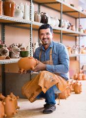 cheerful man potter holding ceramic vessels