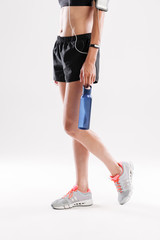 Cropped image of a sportswoman in earphones holding water bottle