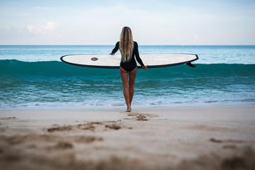Beautiful young woman in bikini with surf board at beach of tropical island.