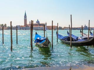 Gondolas moored in the Venetian lagoon. Venice, Italy