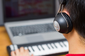 back of asian man listening music and playing midi keyboard with laptop computer, focus on headphone