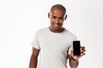 Cheerful young african man showing display of mobile phone.