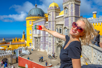 Happy woman takes photo of Pena National Palace in Sintra, by mobile phone with Portugal flag cover. Tourism and travel in Portugal. Female lifestyle takes pictures with her smartphone.Blur background